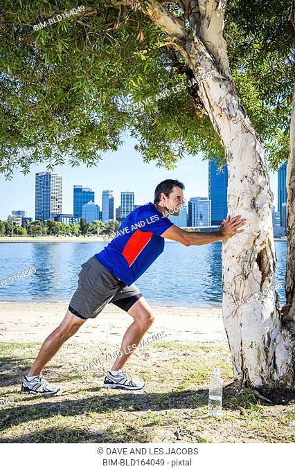 Caucasian runner stretching at tree near Perth city skyline, Western Australia, Australia