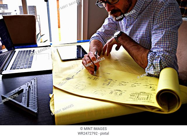 High angle view of an architect working on a technical drawing