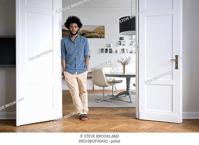 Man at home standing in door frame in living room