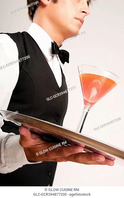 Close-up of a waiter holding a cocktail on a tray
