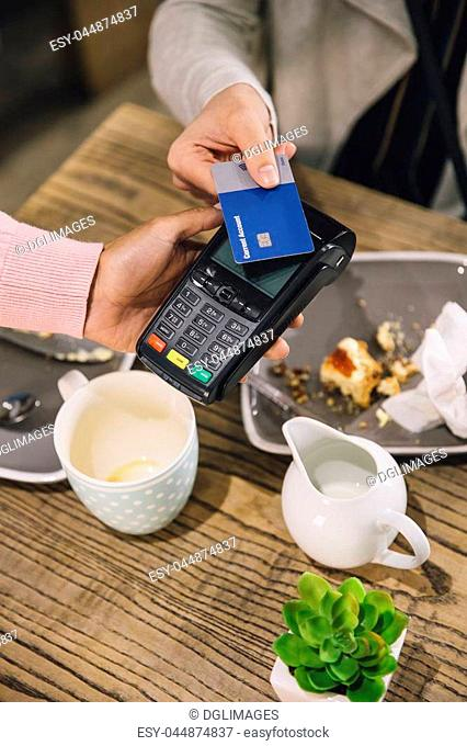 High angle view of a woman making a contactless card payment for her coffee and scone in a cafe