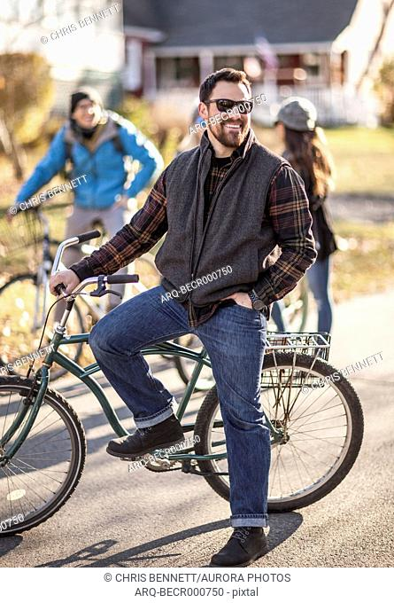 Portrait of bearded man wearing sunglasses standing with bicycle and smiling, Portland, Maine, USA