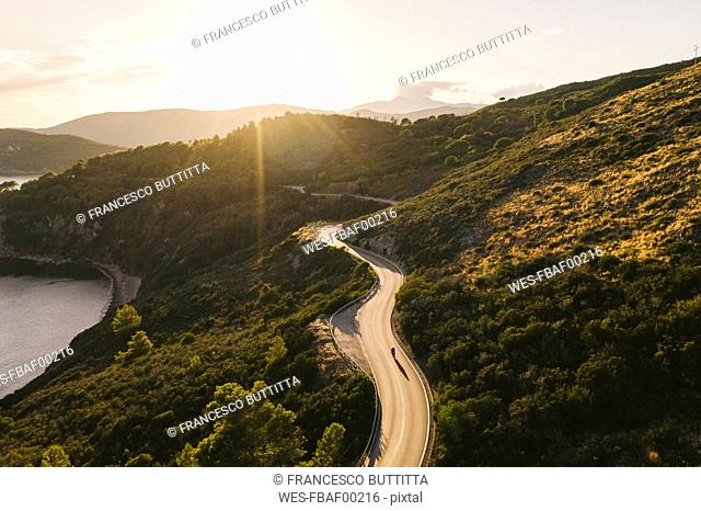 Italy, Elba Island, biker on coastal road against the sun, aerial view with drone