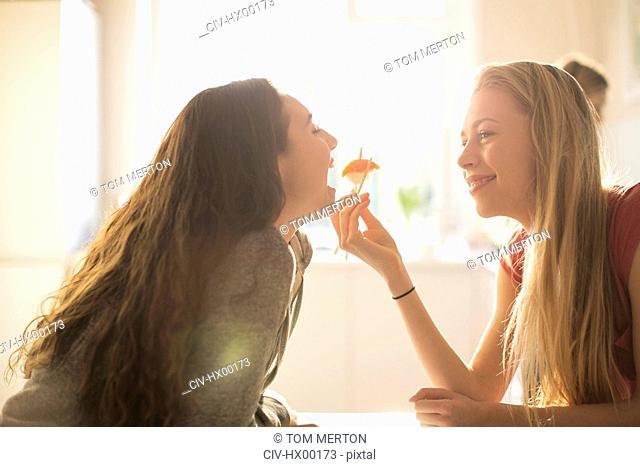 Teenage girl feeding friend sushi with chopsticks
