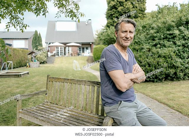 Portrait of smiling mature man in garden of his home