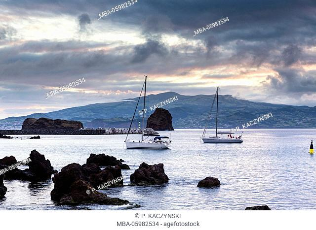 Lava rocks and moored sailing boats in front of the silhouette of Faial at a dramatic sunset