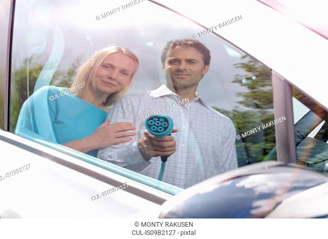 Reflection of man and woman with electric, car holding charging plug