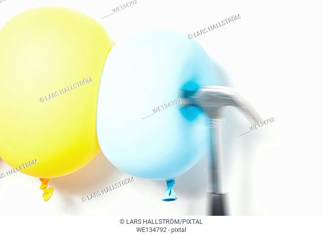 Hammer hitting balloons. Conceptual image of contrasts, resistance and strength