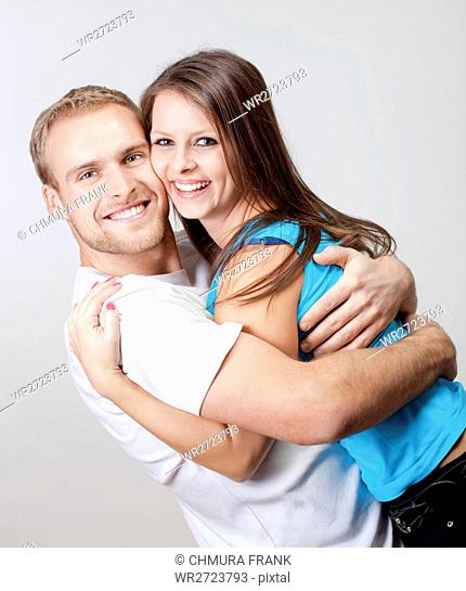 portrait of a happy young couple smiling, looking - isolated on gray