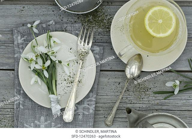 A place setting with snowdrops and a cup of bergamot tea