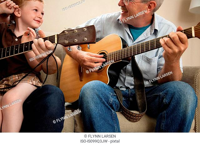Boy and grandfather playing guitar