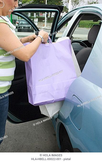Woman placing shopping bags in car
