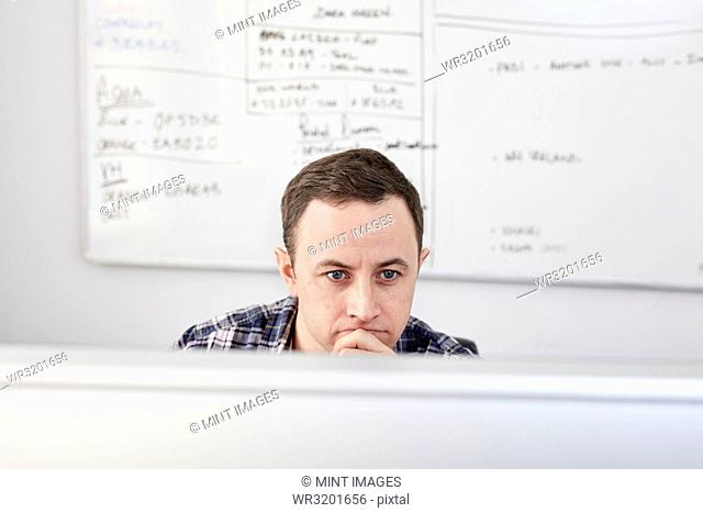 Man looking at a computer screen seated at his desk, with a project chart on the whiteboard behind