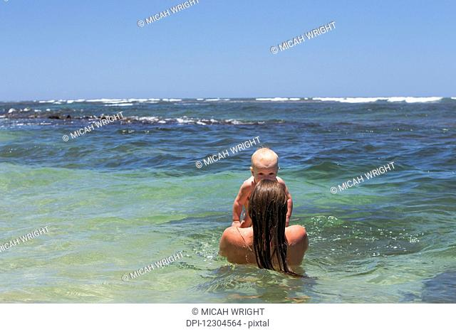 A mother and daughter play in the warm water; Kauai, Hawaii, United States of America