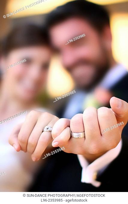 Bride and groom smiling, showing off their wedding rings after their wedding