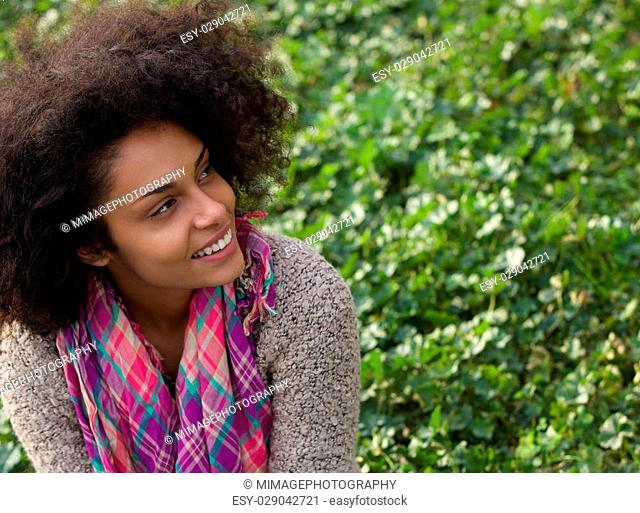 Close up portrait of a smiling african american woman sitting on grass