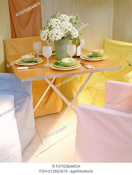 Pastel loose-covers on chairs around folding table set for lunch in economy-style dining room