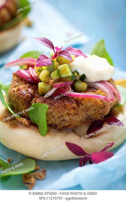 Chickpea burgers on unleavened bread with red onions, cucumber and a yoghurt suace