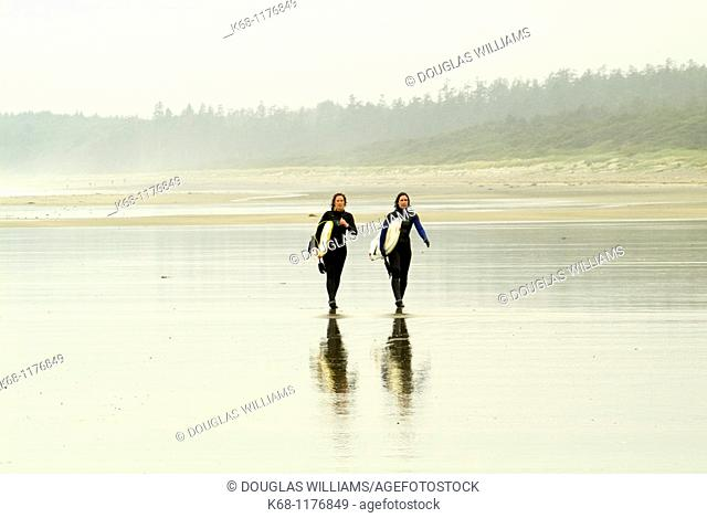 two female surfers carry surfboards on the beach near Tofino, British Columbia, Canada