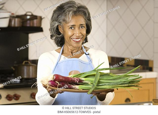Senior African woman holding plate of vegetables