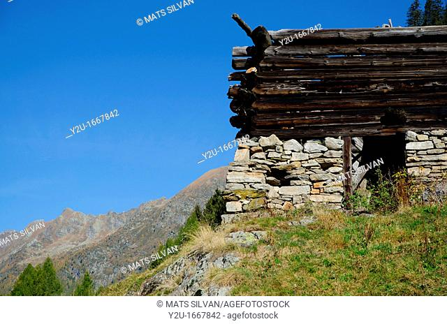 Old broken rustic house on the alps with blue sky