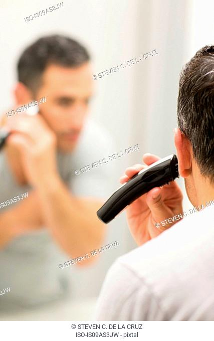 Mid adult man, looking in mirror, using electric shaver, rear view