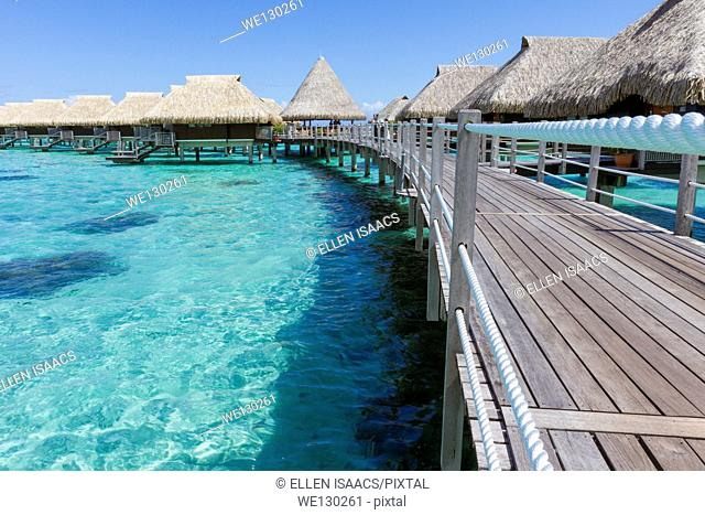 Walkway leading to luxurious overwater bungalows over coral reef in French Polynesia