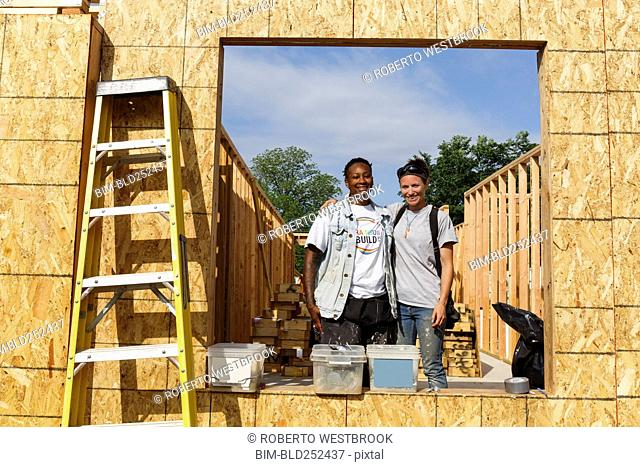 Portrait of volunteers behind window frame at construction site