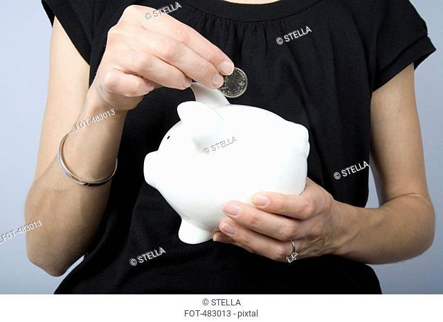 Detail of a woman holding a coin above a piggy bank