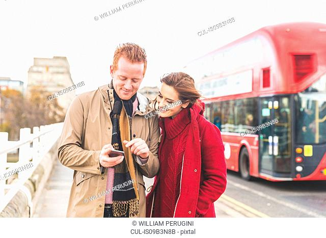 Couple using mobile phone on street, London, UK