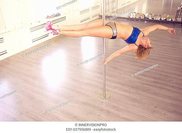 A photo of young woman training on dance pole in horizontal position. She's hanging upside down