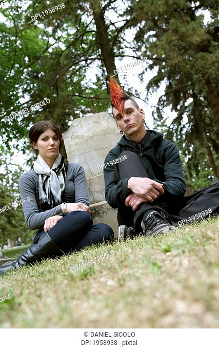 A Young Man And Young Woman Sitting By A Tombstone In A Cemetery; Edmonton, Alberta, Canada