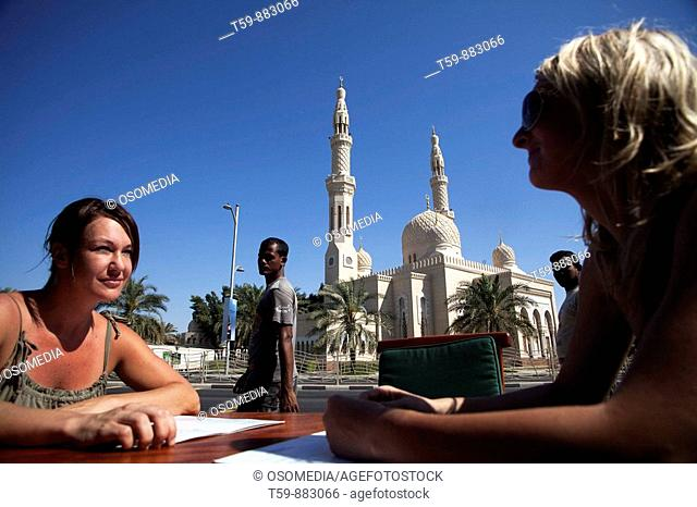 Two european women sitting at café in front of Jumeira Mosque. Dubai City. Dubai. United Arab Emirates