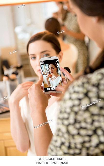 Makeup artist photographing client with cell phone