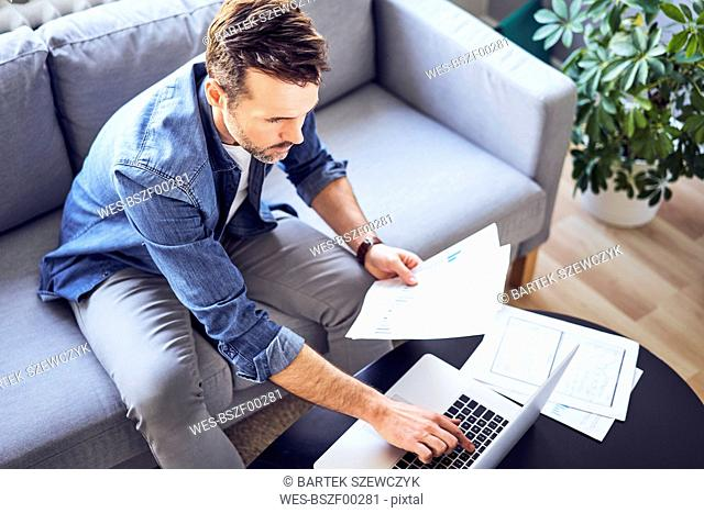 Man with documents sitting on sofa using laptop