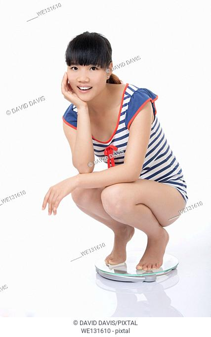 Beautiful Chinese woman weighing herself on a scale and excited with the results isolated on a white background