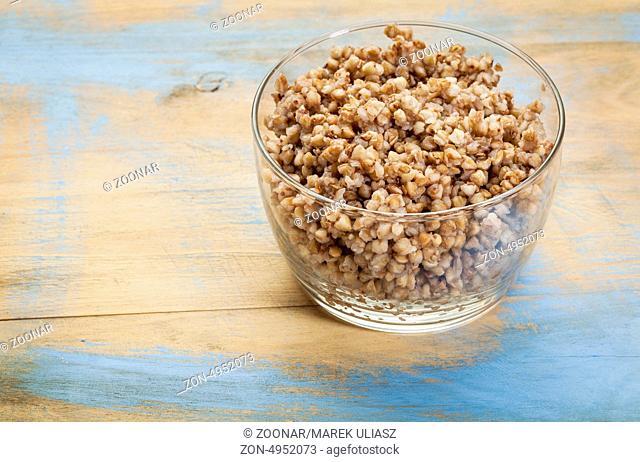 glass bowl of cooked buckwheat kasha on wood background