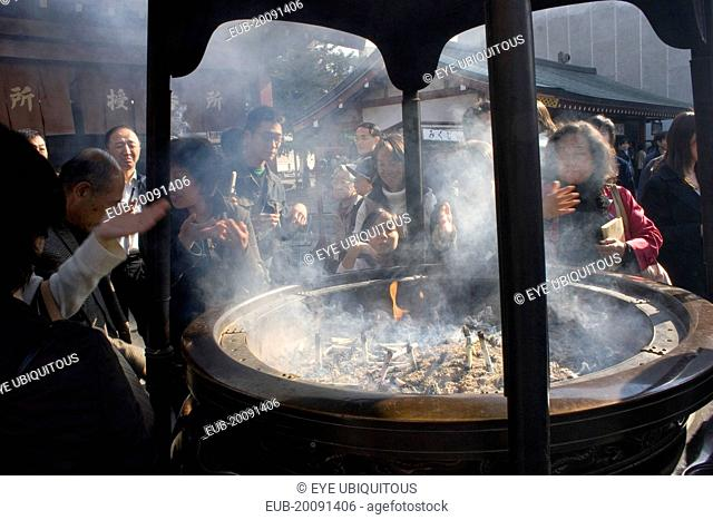 Asakusa Kannon or Senso-ji Temple. Japanese people wafting smoke from incense burner or joukoro over themselves in belief that it will keep them in good health