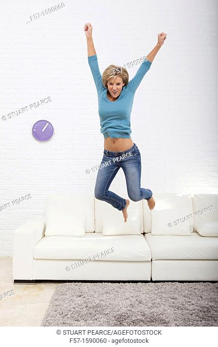 Young woman jumping for joy off her sofa