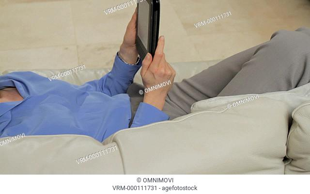 Mature woman reading e-book and lying on sofa, panning from left to right