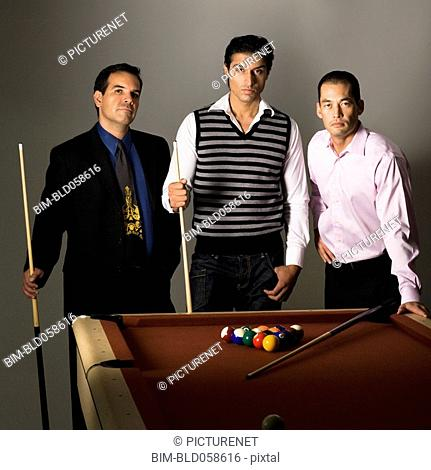 Multi-ethnic men playing billiards