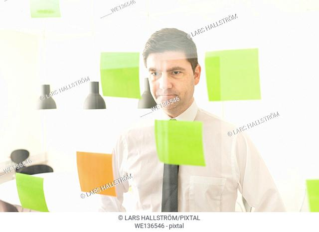 Businessman looking at glass wall with adhesive notes. Conceptual image of business planning and strategy