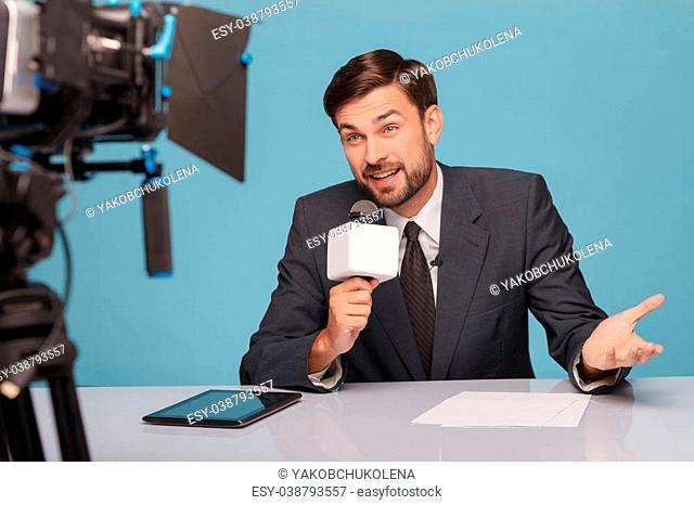 Attractive young male tv newscaster is reporting at studio. He is speaking into a microphone and looking at camera. The man is sitting at the table and smiling