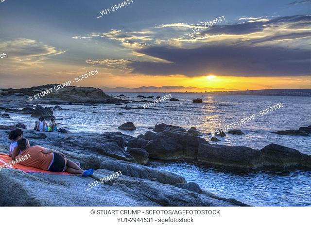 HDR image of people watching the sunset over rocks in the sea on the Spanish island of Tabarca