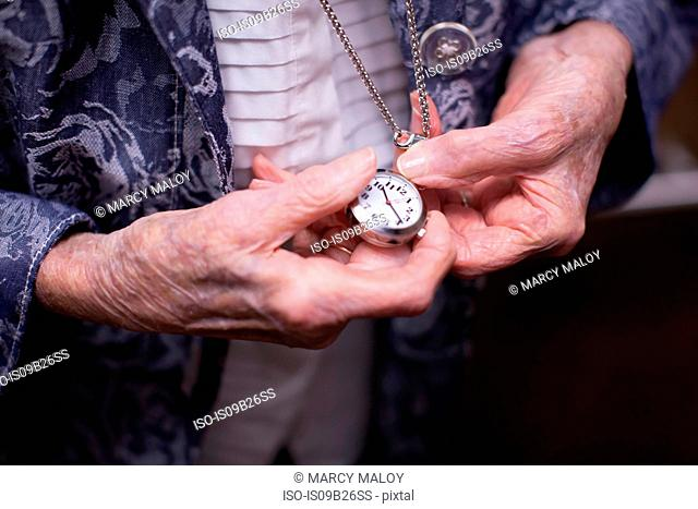 Senior woman, holding pocket watch, mid section, close-up