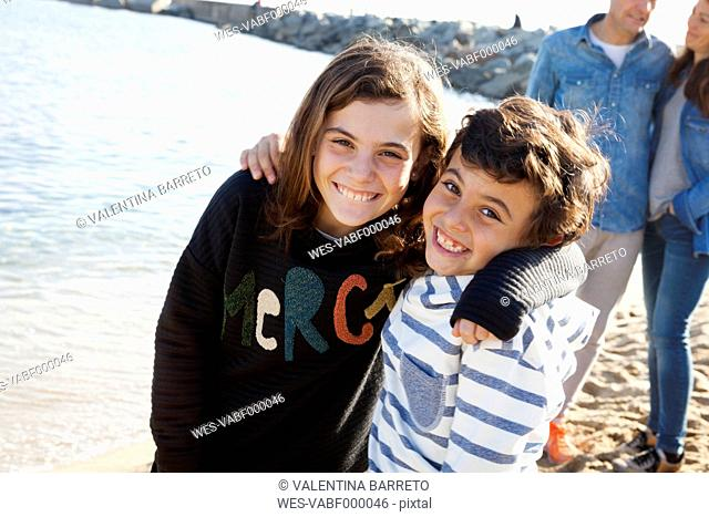Spain, Barcelona, portrait of happy brother and sister on the beach with their parents in the background