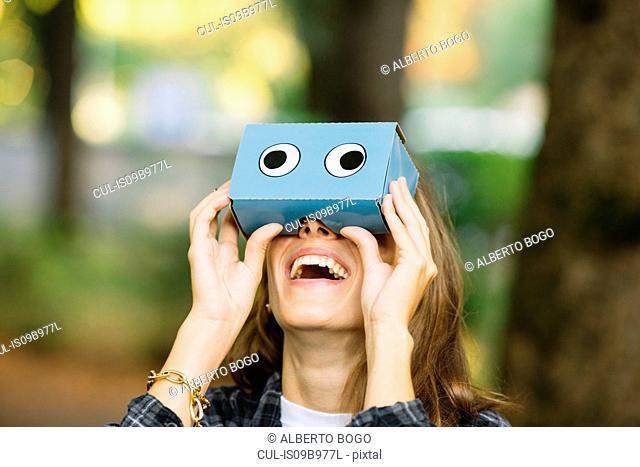Young woman looking up through cardboard binoculars in park
