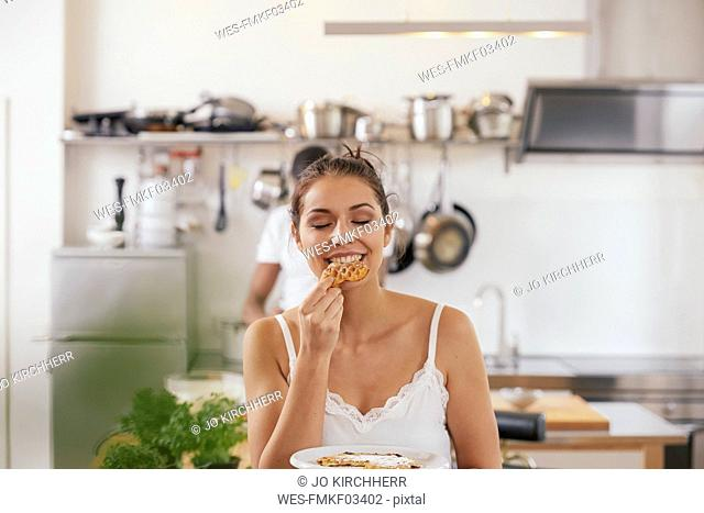 Portrait of young woman eating waffles in the kitchen