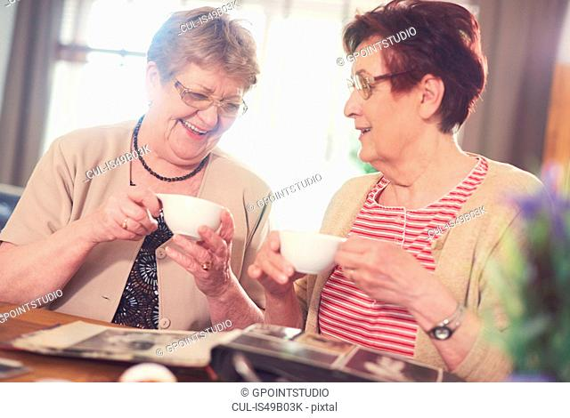 Two senior women laughing while looking at photo album on table