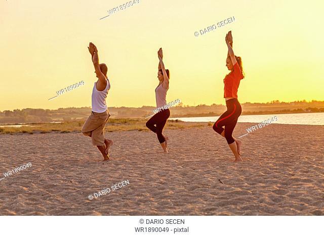 People practising yoga on beach, eagle pose